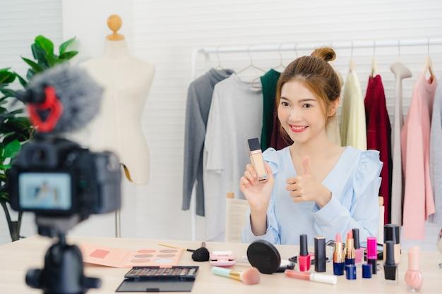 Cosmetici di bellezza presenti di blogger di bellezza che si siedono nella macchina fotografica anteriore per registrare video