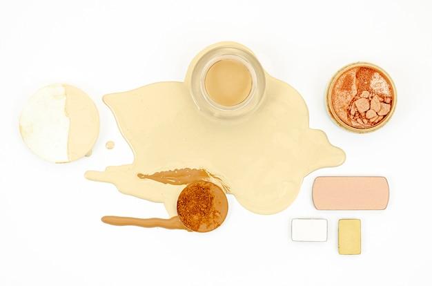 Cosmetici differenti di disposizione piana su fondo bianco
