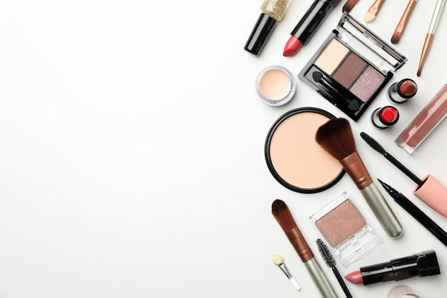 Cosmetici differenti di trucco su fondo bianco, vista superiore
