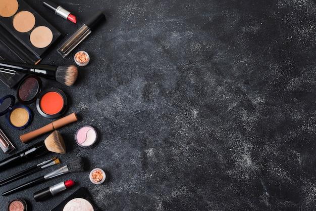 Cosmetici disposti su sfondo scuro polveroso