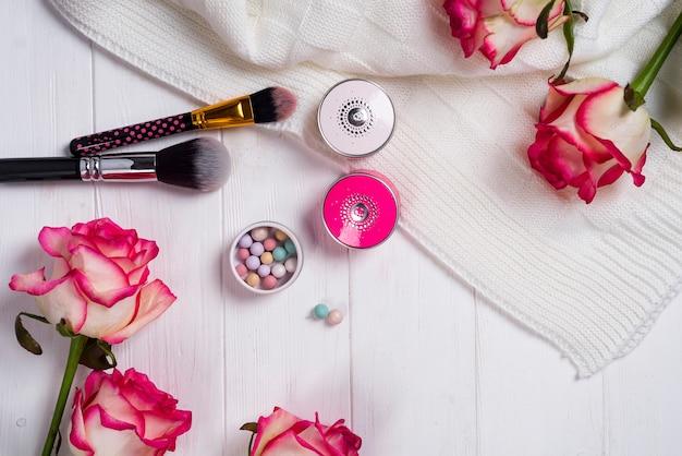 Cosmetici donne e articoli di moda su fondo di legno bianco