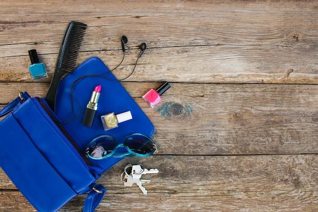 Cosmetici e accessori femminili sono caduti dalla borsetta blu. vista dall'alto.