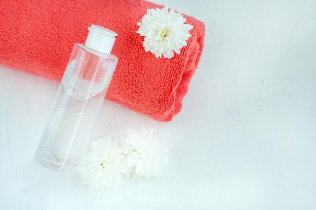 Cosmetici e asciugamano facciali su uno sfondo bianco. il concetto di