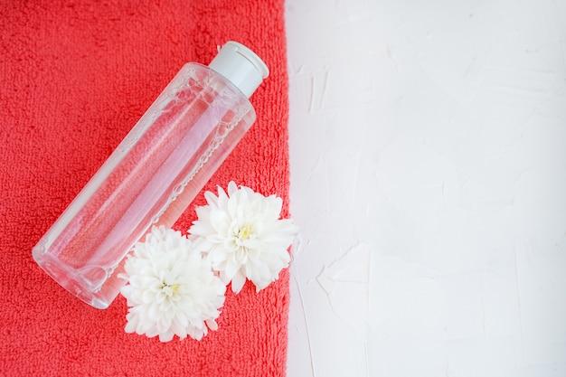 Cosmetici e asciugamano facciali su uno sfondo bianco. vista dall'alto. il c