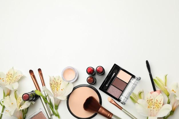 Cosmetici e fiori differenti di trucco su fondo bianco. accessori femminili