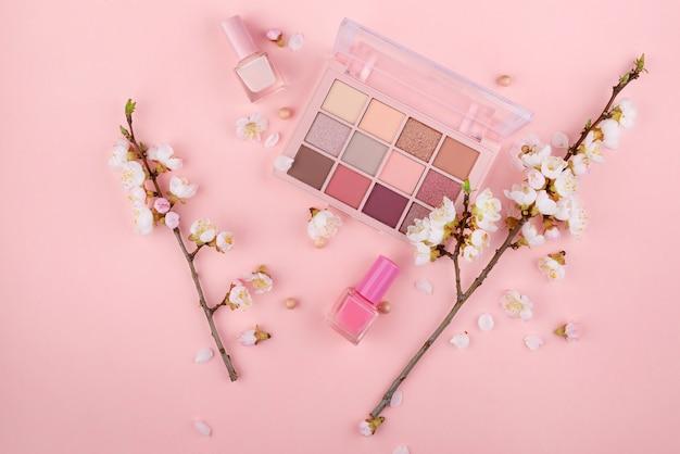 Cosmetici e fiori su uno sfondo rosa con spazio per il testo