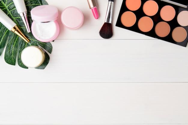 Cosmetici e prodotti per la cura della pelle e foglie verdi sul tavolo di legno bianco