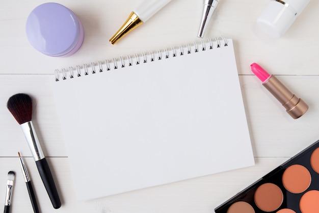 Cosmetici e prodotti per la cura della pelle e notebook sul tavolo di legno bianco