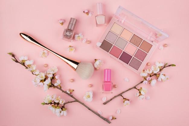 Cosmetici e ramo di sakura su una parete rosa. concetto di bellezza, piatta.