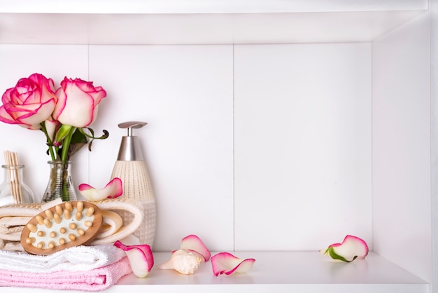 Cosmetici e rosa del bagno della stazione termale sono aumentato, isolato su bianco