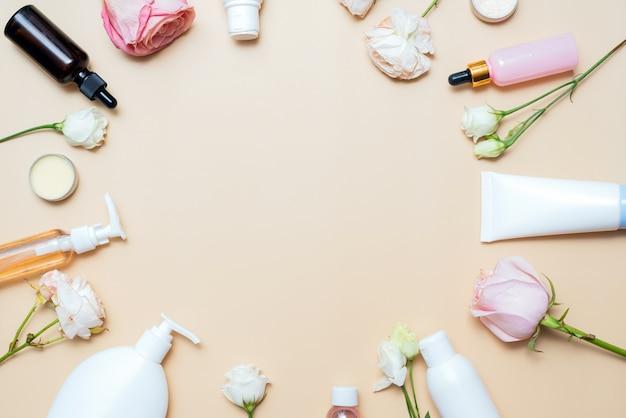 Cosmetici e rose su uno sfondo beige