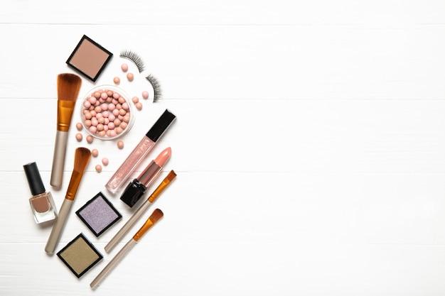 Cosmetici e spazzole decorativi di trucco su una parete bianca, vista superiore. posto per il testo