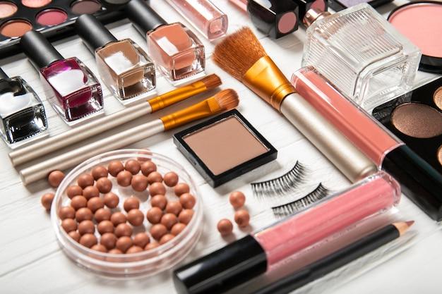 Cosmetici e spazzole decorativi di trucco su una parete bianca, vista superiore