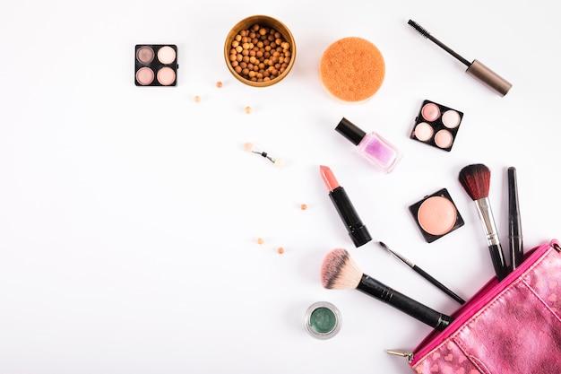 Cosmetici e spazzole di trucco differenti su fondo bianco