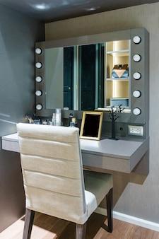Cosmetici e strumenti decorativi sulla tavola di condimento vicino allo specchio nella stanza di trucco
