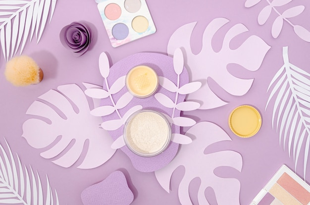Cosmetici femminili su sfondo viola
