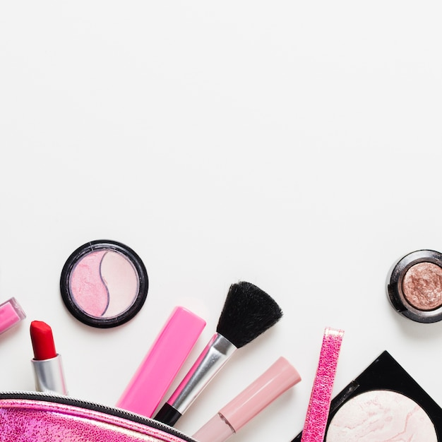 Cosmetici glamour sparsi su sfondo bianco