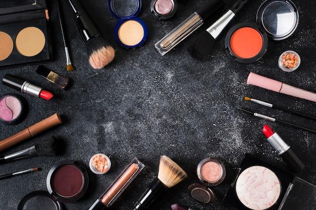 Cosmetici glamour sparsi su sfondo scuro polveroso