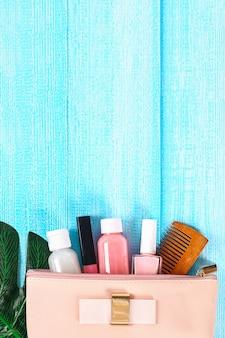 Cosmetici in un sacchetto cosmetico su una superficie di legno blu.