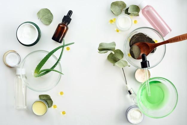 Cosmetici naturali con le foglie e l'olio dell'aloe per derisione bianca del fondo della tavola della stazione termale casalinga su. cosmetici per il viso con lozione dalle erbe sul copyspace bianco di vista superiore del fondo