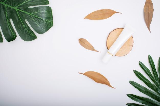 Cosmetici naturali con le foglie su un bianco