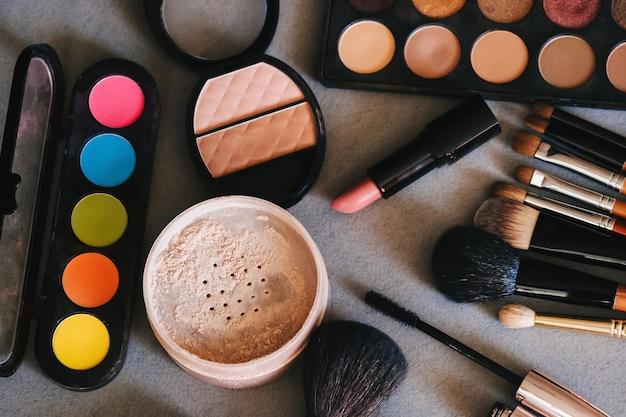Cosmetici per donna per la bellezza e la cura della pelle sul tavolo, pennelli per trucco, palette di ombretti, rossetto, polvere, mascara