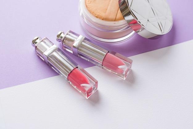 Cosmetici per donna su uno sfondo bianco. disposizione piatta in polvere e rossetto