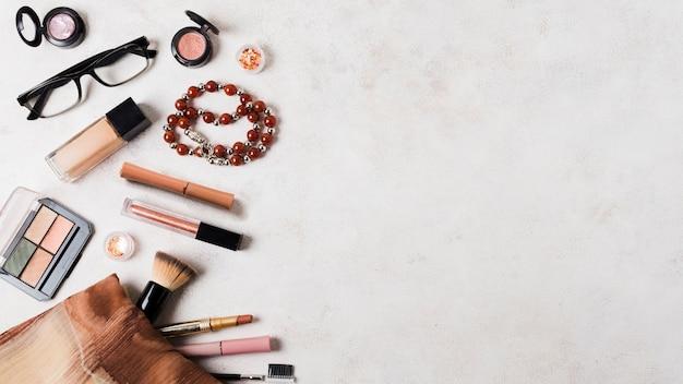Cosmetici per il trucco con accessori sulla superficie chiara