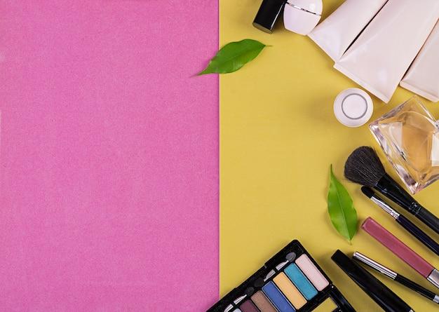 Cosmetici per il trucco su sfondo rosa-giallo. vista dall'alto. copia spazio