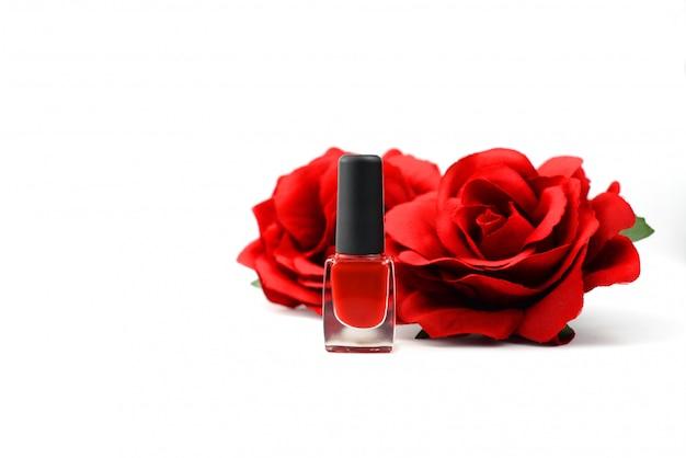 Cosmetici rosso smalto per unghie con fiori rose su uno sfondo bianco