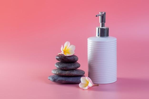 Cosmetici spa. fiori di plumeria su un rosa.