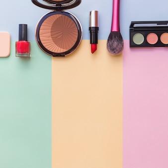 Cosmetici spugna; bottiglia di smalto per unghie; rossetto; tavolozza fard e ombretto su sfondo colorato misto