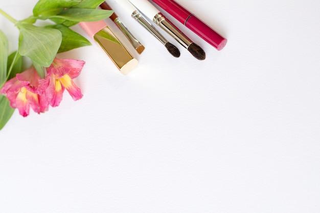 Cosmetici trucco professionale, composizione piatta laici con fiori su sfondo bianco