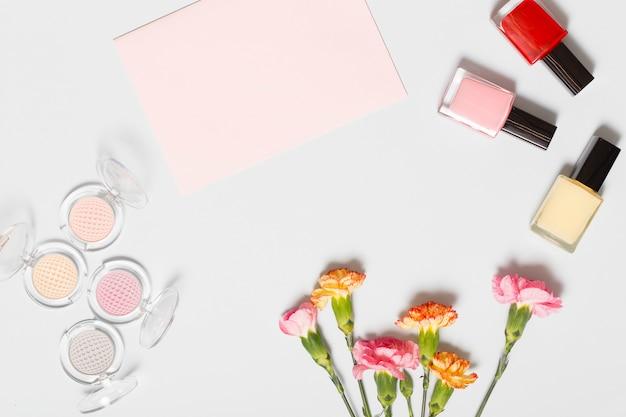 Cosmetici vicino foglio di carta e garofani