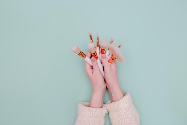Cosmetico professionale della spazzola di trucco nell'estetista femminile della mano sul fondo neo della menta. vista orizzontale superiore copyspace