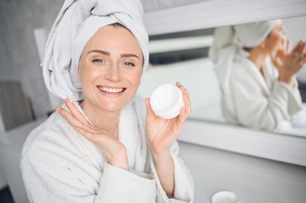 Cosmetologia, cura della pelle, trattamento viso, spa, concetto di bellezza naturale. bella donna sorridente a casa in accappatoio con un asciugamano applicando crema idratante viso dal barattolo bianco. routine di bellezza