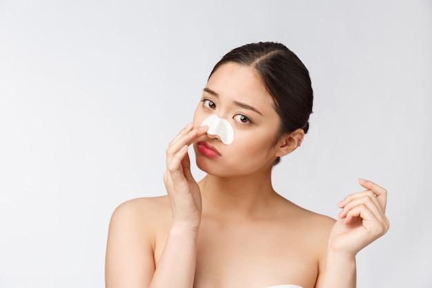 Cosmetologia. ritratto di bella femmina modello asiatico con maschera sul naso. primo piano di giovane donna in buona salute con pelle molle pura e trucco naturale fresco.