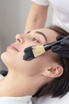 Cosmetologo applicando maschera nera sul viso di una bella donna matura per la desquamazione del carbonio