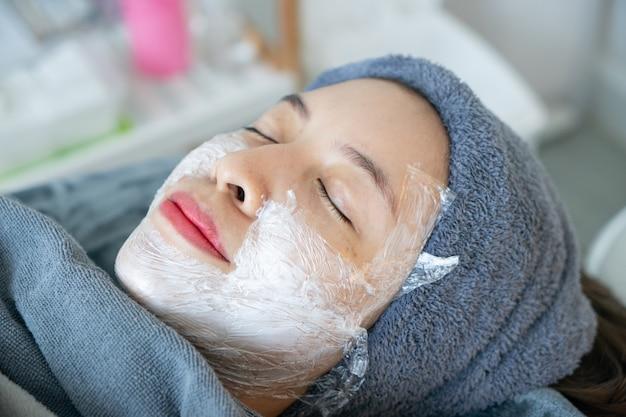 Cosmetologo che applica crema anestetica sul viso della donna prima del laser o delle iniezioni.