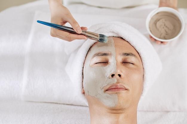 Cosmetologo che applica maschera all'argilla