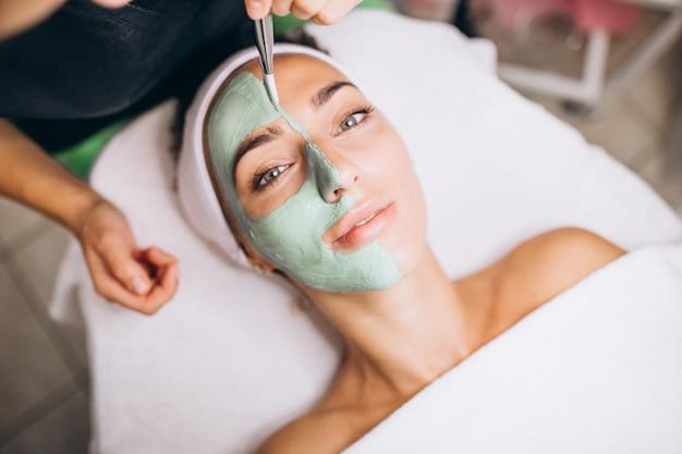 Cosmetologo che applica maschera su una faccia del cliente in un salone di bellezza