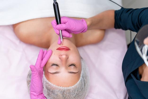 Cosmetologo che applica trucco permanente