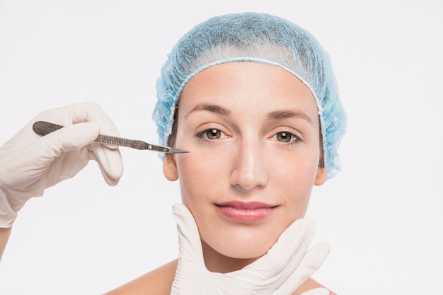 Cosmetologo con bisturi vicino viso di donna
