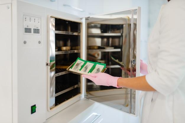 Cosmetologo in guanti mette attrezzature per manicure e pedicure nell'armadietto antibatterico