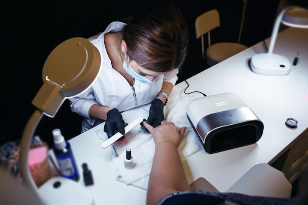 Cosmetologo in una maschera protettiva, che elabora le unghie sulla mano del cliente