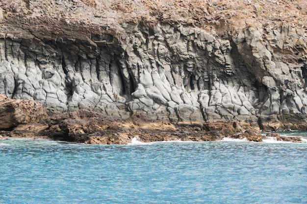 Costa rocciosa a lunga gittata con acqua cristallina