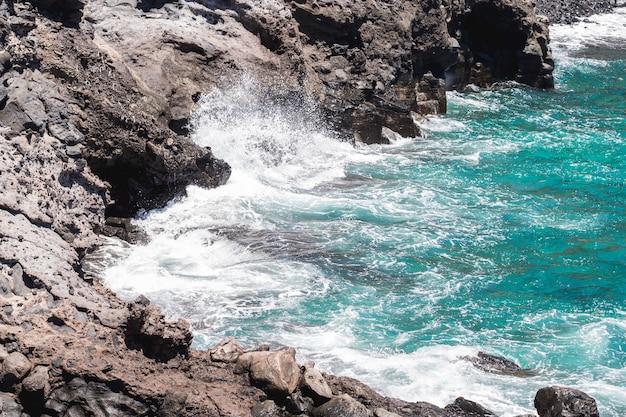 Costa rocciosa del primo piano con acqua cristallina