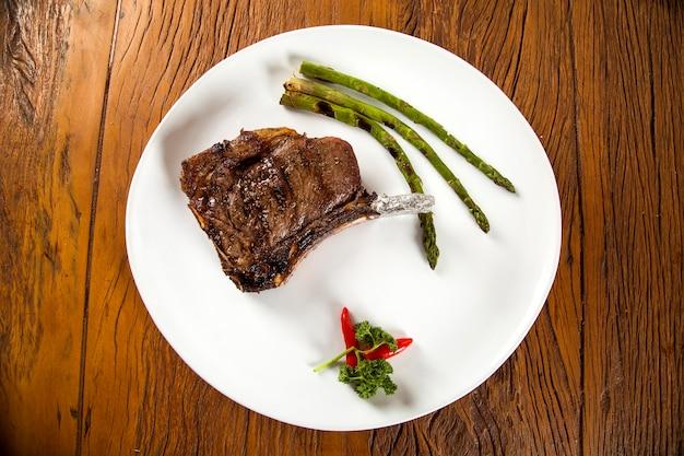Costine di carne alla griglia su piatto bianco con pomodori erba cipollina e salsa piccante scura a bordo