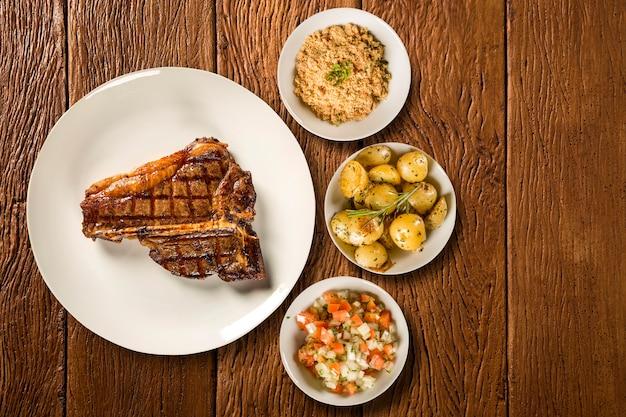 Costine di carne alla griglia sulla zolla bianca con patate, farina e vinaigrette.