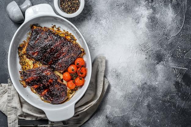 Costine di maiale alla brace. carne grigliata. sfondo grigio. vista dall'alto. spazio per il testo
